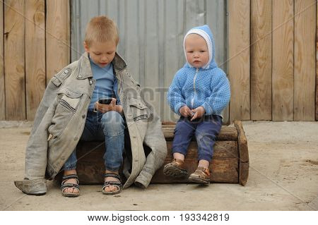 Two young guy plays with a phone and a prize for races on a rural farmstead in a hot summer