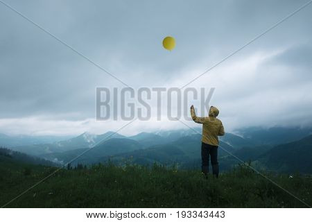 Man with yellow balloon in higt mountains