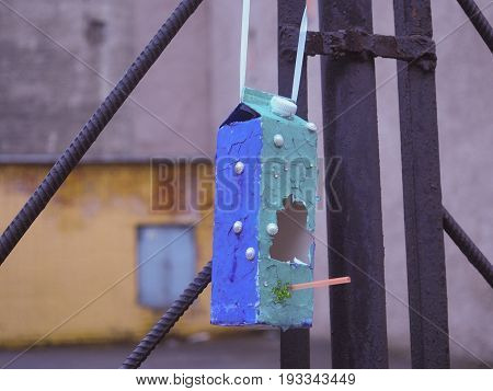 A stylish birdfeeder made of milk pocket and painted with blue paint hanging on the fence