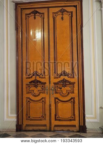 A wooden door of red polished wood with beautiful decorations