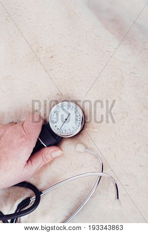 Useful device for my health care. Confident ill aging woman sitting on the bed at home and measuring blood pressure while holding tonometer