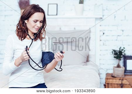 Testing new health care device . Pleasant skilled young woman sitting on the bed at home and measuring blood pressure while holding tonometer