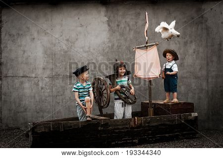 Three cute boys on pirate ship as sailors on a summer day