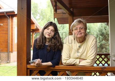 grandmother with granddaughter close up photo on the wooden country porch