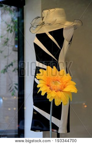 Striking black and white fashionable dress on mannequin in  storefront window invites people to come in and try an article on.