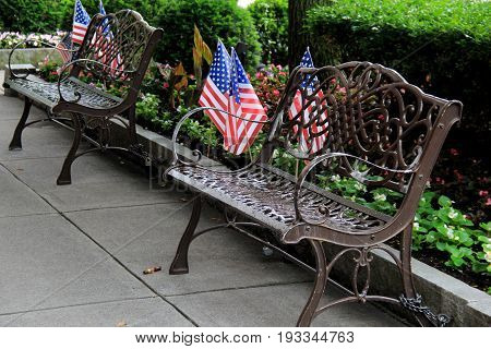 Line of metal park benches for sitting, with American flags