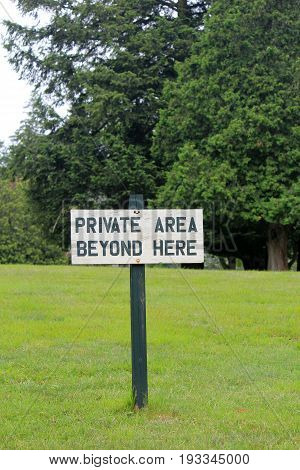 Vertical image of hand-painted sign on wooden post that reads 'private  area beyond here.'