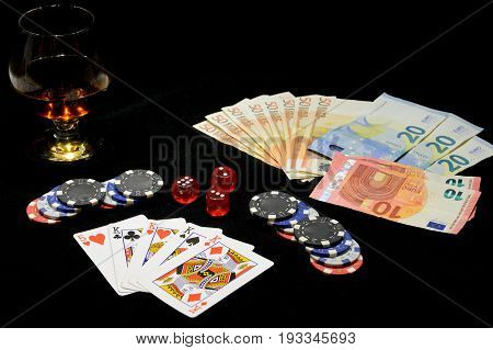 playing cards, chips, money bills and a glass of cognac on a black background