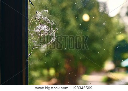Bullet hole in the dirty window glass