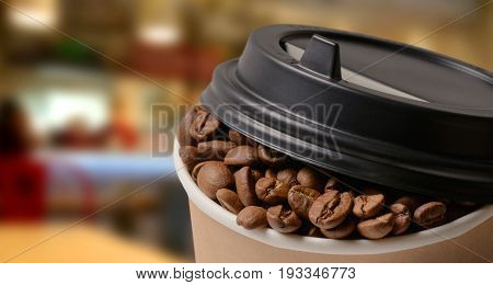 Paper Coffee cup and Coffee Beans with blur coffee shop background . Takeaway or Disposable Coffee Cup