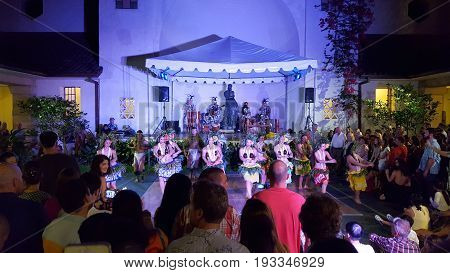 HONOLULU - MAY 27: Hula dancers dance as musicians play on stage with crowd watching at Art After Dark event at the Honolulu Museum of Art on May 27 2016 Oahu Hawaii.