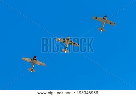EDEN PRAIRIE MN - JULY 16 2016: Three AT6 Texan airplanes fly directly overhead against clear sky at air show. The AT-6 Texan was primarily used as trainer aircraft during and after World War II.
