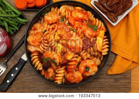 Shrimp Fusilli Pasta with Carrots, Green Beans, Cranberry Juice and Barley Apricot Crisp at table.
