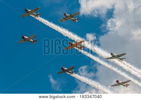 EDEN PRAIRIE MN - JULY 16 2016: Seven AT6 Texan airplanes fly overhead in cloudy sky with smoke trails at air show. The AT6 Texan was primarily used as trainer aircraft during and after World War II.