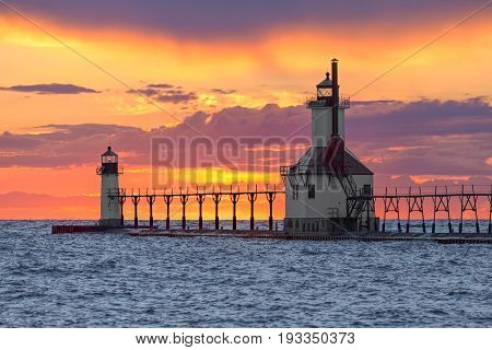 The St. Joseph Michigan North Pier Inner and Outer Lighthouse shine their lights backed by a dramatic and colorful sunset on Lake Michigan.