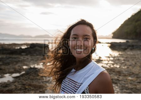 EL NIDO, PALAWAN, PHILIPPINES - MARCH 29, 2017: Portrait of mixed race woman at the sunset in Las Cabanas Beach.