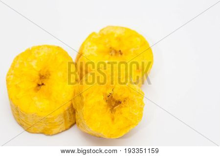 Plantain pieces cross-wise cut to prepare patacones on white background