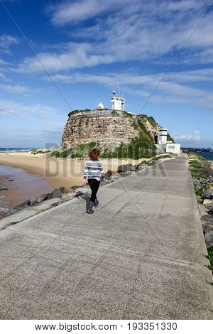 A woman walking along the breakwall at Nobbys Head - Newcastle Harbour. Newcastle is Australia's second oldest city and areas such as Nobbys Lighthouse are popular local landmarks.