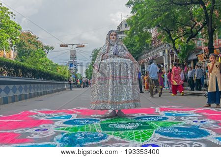 KOLKATA WEST BENGAL INDIA - JUNE 25TH 2017 : Devotee dressed in traditional dress posing on coloured road on the eve of Rath Yatra festival. God Jagannath Balaram and Goddess Suvadra are taken for a chariot ride.