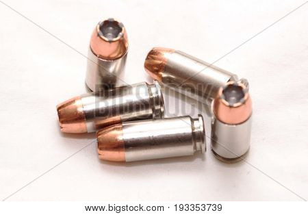 Five 40 caliber hollow point bullets with a white back ground