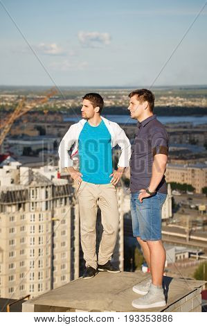 Two roofers on the roof of a high-rise building admire the view of the city. Courage and adrenaline.