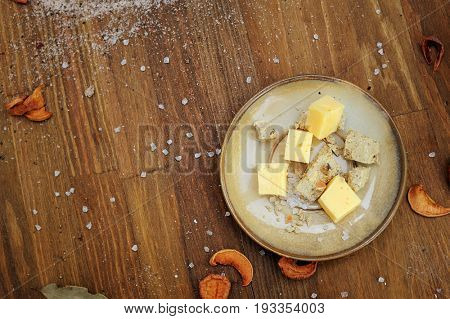 Authentic cheese cubes on a plate, dark wooden horizontal kitchen background, empty space for text, top view
