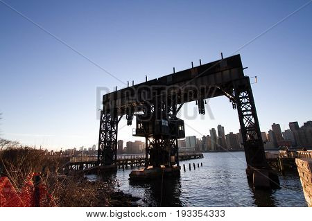 Transfer bridges, support gantries, and piers at Gantry Plaza State Park before sunset