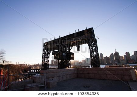 Transfer bridges, support gantries, and piers at Gantry Plaza State Park in silhouette before sunset