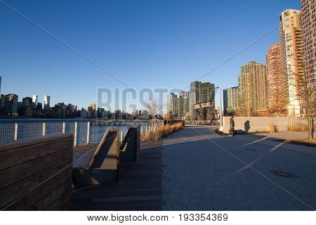 Walkway and bench at Gantry Plaza State Park with blue sky
