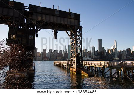 Transfer bridges, support gantries, and piers at Gantry Plaza State Park with sunset sky