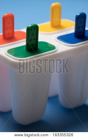 Closeup of ice cream lolly maker form with colorful sticks over blue background