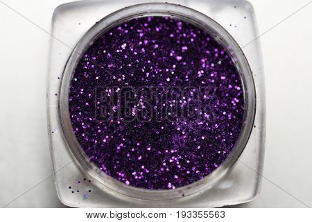 Closeup of purple nail makeup glitter in round jar isolated on silver background. Concept of beauty and makeup
