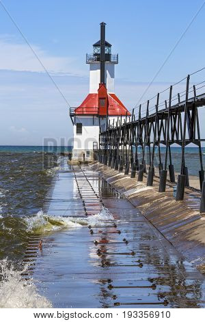 Lake Michigan waves splash over the breakwater at the St. Joseph Michigan Lighthouse.