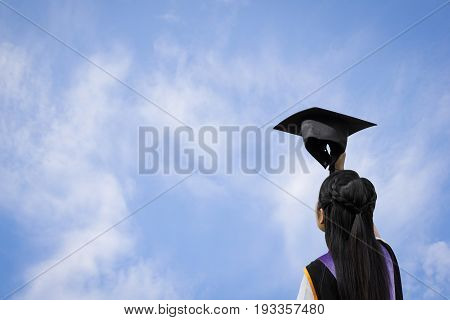 Stock Photo - Back view of graduate student girl with hand holding hat up to the sky.