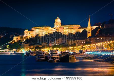 Evening View Of Buda Castle With City Lights And Ship On The Danube River