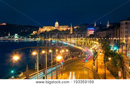 Evening View Of Buda Castle With City Lights And Ship On The Danube River.