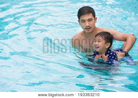 Playful father and son having fun in water.
