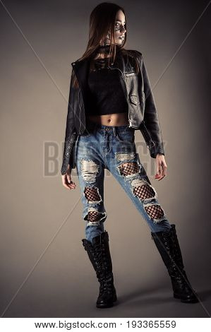 beautiful fashionable teenager girl in leather jacket and torn jeans