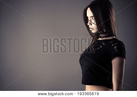 fashionable cyberpunk girl with lace choker isolated on gray background