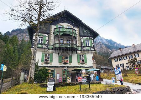 Fussen, Germany - December 27, 2016: Beautiful painted traditional bavarian house and german alps in Bavaria