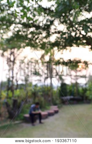 Blurred image of a man sitting in park waiting or relaxing concept background.