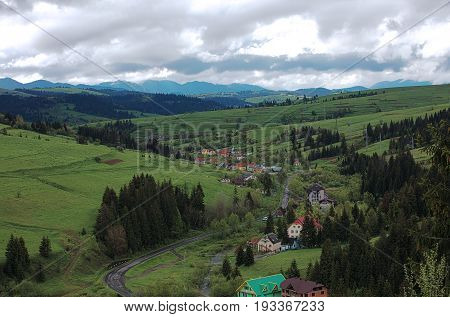 A winding road passes through the village in the valley of the Carpathians.