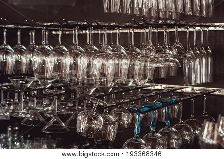 raws of glasses for a margarita, martini, grog and liqueur hanging upside down in bar at arestaurant, dark background