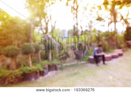 Blurred image of a man sitting in park waiting or relaxing concept background warm tone photo.