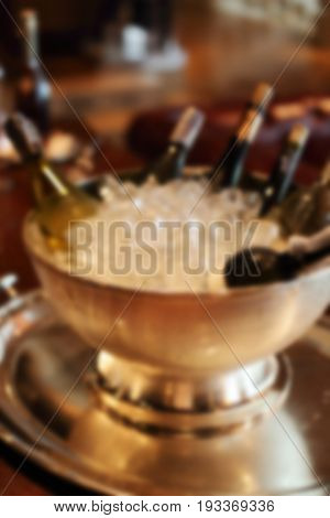 Blurred image of wine bottles in silver cold ice bucket.