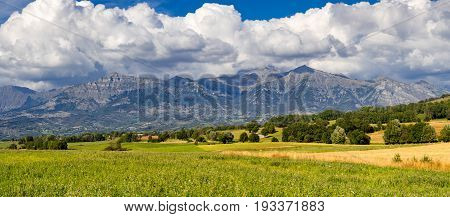 Panoramic view of the Champsaur Valley from the Manse Pass in summer. The view includes the villages of Saint-Michel-de-Chaillol and Saint-Julien-en-Champsaur and the mountain peaks Queyrel Peak Touron Peak Soleil Boeuf and Palastre. Hautes-Alpes PACA Reg