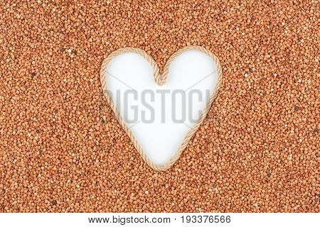 Buckwheat grains and a rope in the shape of a heart with a place for designers. The concept of love of buckwheat