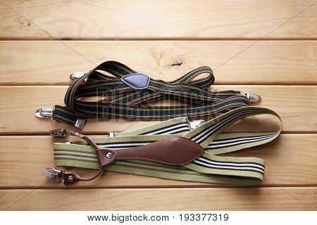 Two Pairs of Trousers Braces on Wooden Background