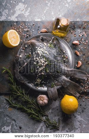 Raw flounders with different seasoning on the stone background top view vertical
