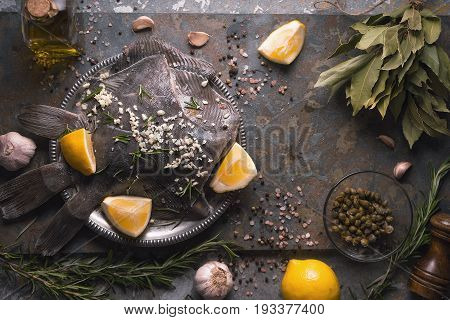 Raw flounders with different seasoning on the stone background top view horizontal
